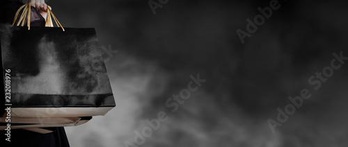 Czarny Piątek sprzedaży pojęcie młodej kobiety mienia torba na zakupy na ciemnym tle z kopii przestrzeni mody stylem
