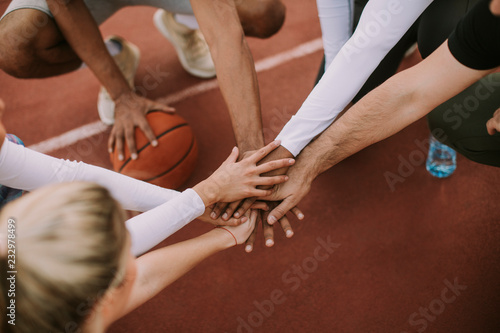 Top view of basketball team holding hands over court