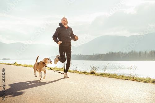 Poranny jogging ze zwierzakiem: mężczyzna biegnie razem ze swoim psem beagle