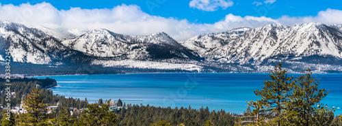 Panoramiczny widok w kierunku jeziora Tahoe w słoneczny, pogodny dzień; w tle pokryte śniegiem góry Sierra; wiecznie zielone lasy na pierwszym planie