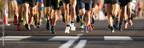 Maratończycy biegający po drogach miejskich, duża grupa biegaczy