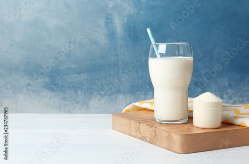 Protein shake in glass and powder on table. Space for text