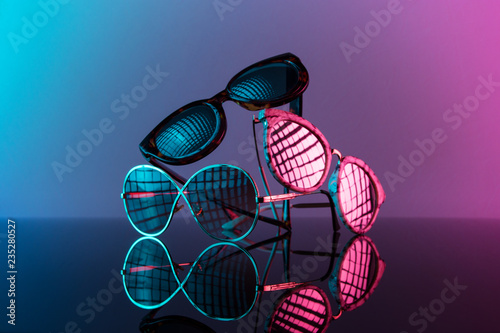 Okulary przeciwsłoneczne ułożone w stos z żywym kolorem, gorącym różem i niebieskim.