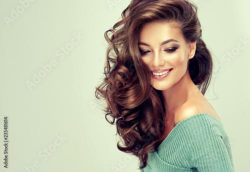 Piękna modelka z długimi falującymi i lśniącymi włosami. Brunetki kobieta z kędzierzawą fryzurą