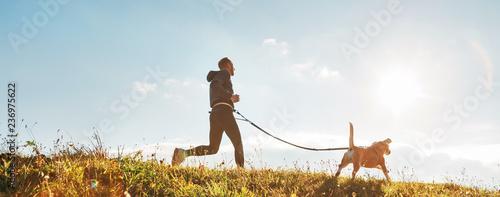 Ćwiczenia Canicross. Mężczyzna biegnie ze swoim psem beagle w słoneczny poranek. Pojęcie zdrowego stylu życia.