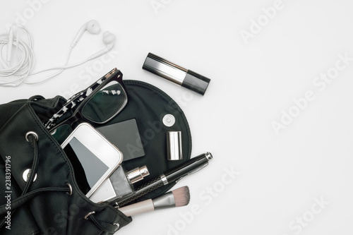Top view of woman black bag open out with accessories smartphone, perfume, pens, cosmetics, earphone and glasses on white background