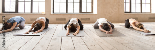 Pięć dziewcząt podczas sesji jogi w studio sportowym. Sportowe kobiety leżące w szeregu relaksujące się na drewnianych podłogowych gumowych matach robią dziecko pozę. Poziomy baner fotograficzny do nagłówka strony. Koncepcja odnowy biologicznej