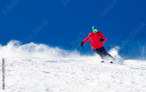 Człowiek na nartach na przygotowanym stoku ze świeżym, nowym śniegiem