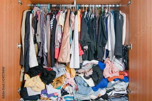 Kupa niechlujnych ubrań w szafie. Nieładna, zagracona szafa kobiety.