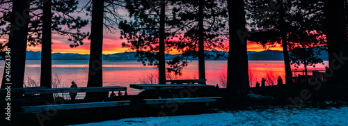 People enjoying an amazing sunset on the shoreline of Lake Tahoe; pine trees silhouettes in the foreground, California