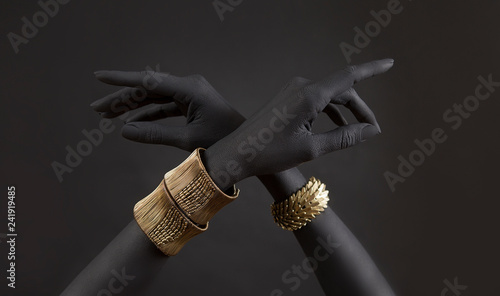 Black woman's hands with gold jewelry. Oriental Bracelets on a black painted hand. Gold Jewelry and luxury accessories