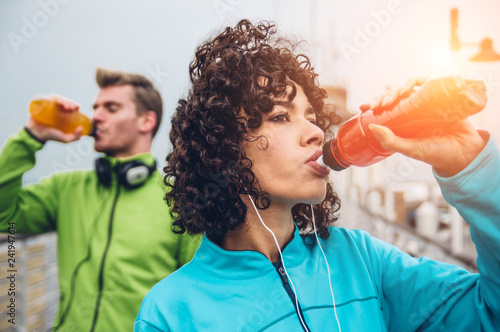 Sporty runners couple drinking energy drink