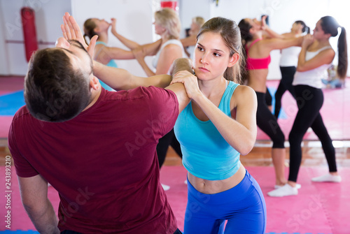 Sportowa kobieta z trenerem wykonuje ruchy samoobrony na siłowni