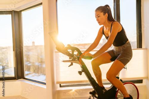 Domowy trening fitness kobieta trenująca na inteligentnym rowerze stacjonarnym w pomieszczeniu oglądająca ekran podłączony online do usługi subskrypcji transmisji strumieniowej na żywo do ćwiczeń rowerowych. Młoda kobieta Azji sportowiec.