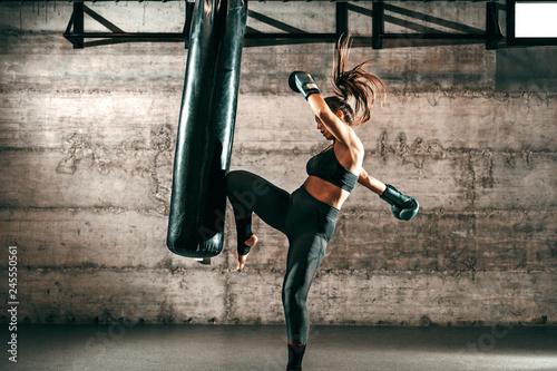 Dedykowana silna brunetka z kucykiem, w odzieży sportowej, boso i w rękawicach bokserskich kopiąc worek na siłowni.