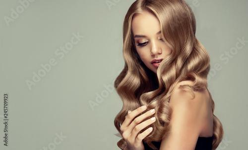 blondynka z długimi i lśniącymi falującymi włosami. Piękny uśmiechnięty kobieta model z kędzierzawą fryzurą.