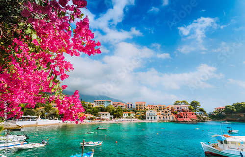 Beautiful Assos village scenery framed with branch of magenta blossom fuchsia flower. Summer vacation concept