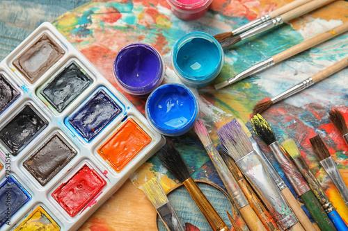 Różne pędzle i farby na palecie kolorów, widok z góry