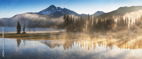 South Sister i Broken Top odbijają się nad spokojnymi wodami jeziora Sparks o wschodzie słońca w Cascades Range w środkowym Oregonie, USA, w świetle wczesnego poranka. Poranna mgła unosi się z jeziora w drzewa.