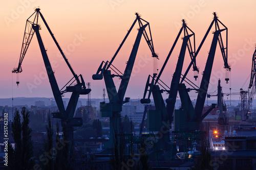 Gdańsk, Polska. Sylwetki dźwigów portowych o zachodzie słońca