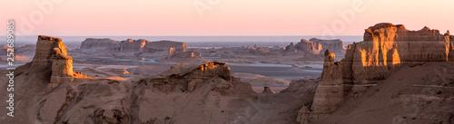 Panoramic view of sandy mountains in Kaluts desert, part of Dasht-e Lut desert during sunrise, Iran