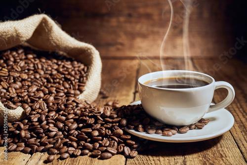 Czarna kawa na starych deskach i rozsypane ziarna