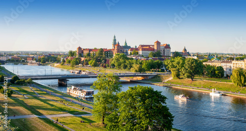 Poland. Krakow aerial panorama with historic royal Wawel castle and cathedral, Vistula river with a bridge, boats, on board restaurant. Promenades and parks along the riversides. Sunset light