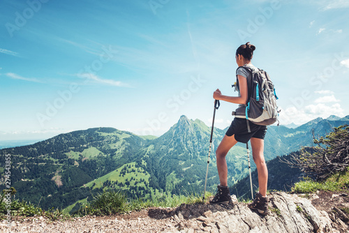 Fit female hiker standing on a mountain ridge