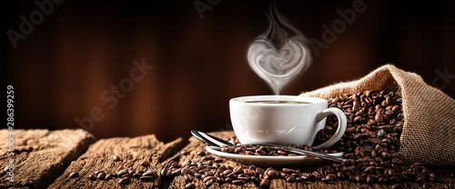 Biała filiżanka gorącej kawy z parą w kształcie serca na starym wyblakłym stole z jutowym workiem i fasolą