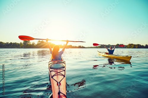 People kayak during sunset in the background. Have fun in your free time.