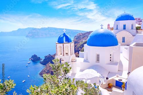 Piękny miasteczko Oia na wyspie Santorini, Grecja. Tradycyjna biała architektura i greckie cerkwie z niebieskimi kopułami nad kalderą na Morzu Egejskim. Malownicze tło podróży.