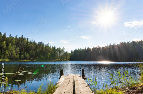 Traditional Finnish and Scandinavian view. Beautiful lake on a summer day and an old rustic wooden dock or pier in Finland. Sun shining on forest and woods in blue sky.