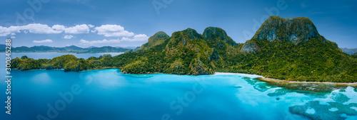 Widok z lotu ptaka na bezludną tropikalną wyspę z surowymi górami, dżunglą lasów tropikalnych, piaszczystymi plażami otoczonymi błękitnym oceanem