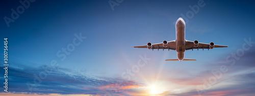 Samolot komercyjny lecący nad dramatyczne chmury podczas zachodu słońca.