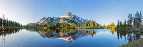 Wulkaniczna góra w ranku świetle odbijał w spokojnych wodach jezioro.