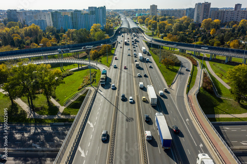 Drone shot at a highway with a clover junction with bridges and ramps, heavy traffic. Warsaw, Poland. Aerial view at the intersection of a large road in Warsaw, with traffic.