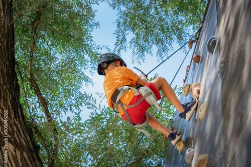 Kid climbing the wall outdoors.