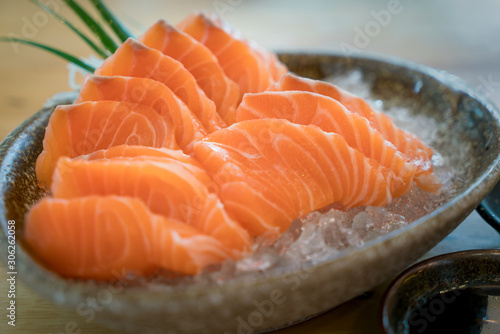 Raw salmon slice or salmon sashimi in Japanese style fresh serve on ice in bowl. Japanese traditional food or with low calories and high nutrition and healthy diet dish.
