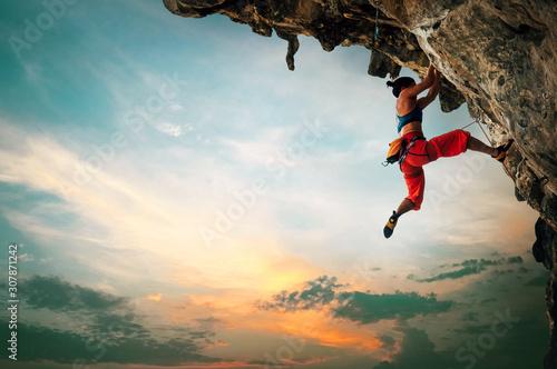 Sportowy kobiety pięcie na nawisłej falezy skale z zmierzchu nieba tłem.