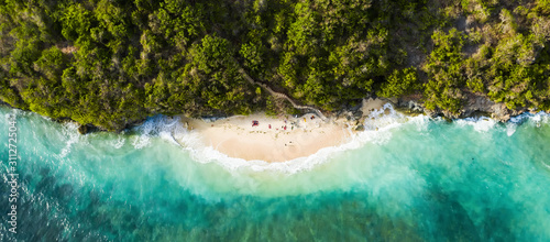 View from above, stunning aerial view of some tourists sunbathing on a beautiful beach bathed by a turquoise rough sea during sunset, Green Bowl Beach, South Bali, Indonesia.