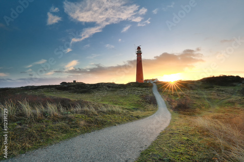 path to red lighthouse at sunrise