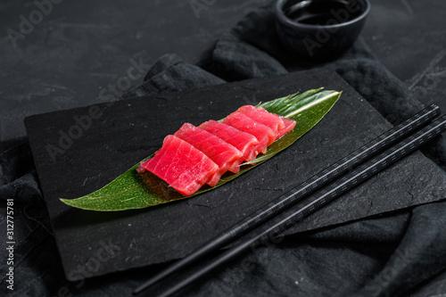 Fresh raw sashimi tuna on a stone Board. Black background. Top view