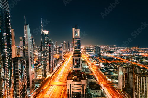 Night view of the spectacular landscape of Dubai with high-rises and skyscrapers at the Sheikh Zayed highway. Global travel destinations and real estate concept