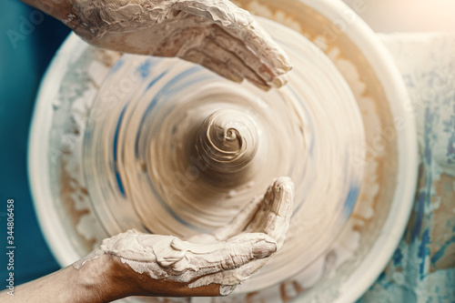 Close-up of female hands sculpting clay on a Potter's wheel. Concept of hobby and cretivity at home and in the Studio workshop