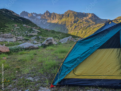 Kemping na łonie natury z namiotem rozbitym wokoło gór w letni słoneczny dzień
