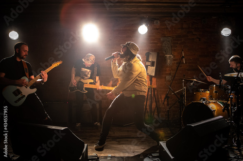 WIDE Punk rock band playing music during their concert on a stage of small venue. Vocals, guitars and drums. Shot with 2x anamorphic lens