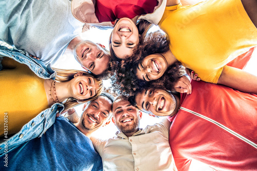 Multiracial group of young people standing in circle and smiling at camera - Happy diverse friends having fun hugging together - Low angle view