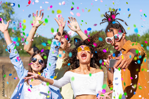 Happy excited friends having fun outdoor celebrating with confetti - Young millenial people enjoying summertime together at garden party - Cheerful friendship concept. Party - festival concept.