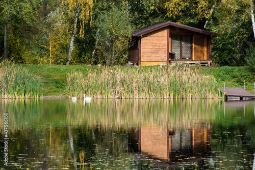 Domek letniskowy, drzewa i dzikie zarośla odbijające się w jeziorze, kolory jesieni