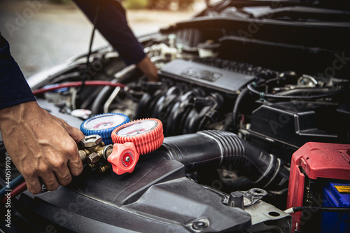 Technician auto mechanic use measuring manifold gauge for filling car air conditioner for fix and checking for repair maintenance and check refrigerant during car periodic inspection service